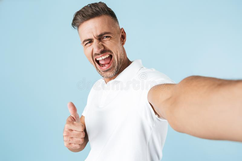 Knappe jonge mens die witte t-shirt status dragen stock afbeelding
