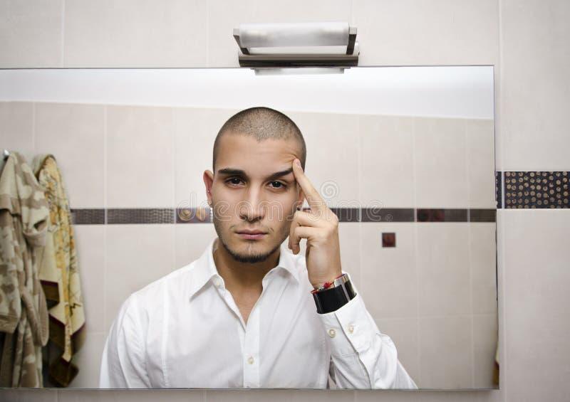 Knappe jonge mens die zich in badkamersspiegel bekijken royalty-vrije stock afbeeldingen