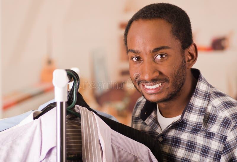 Knappe jonge mens die zich binnen garderobe bevinden die door rek van verschillende overhemden gaan die, manierconcept hangen stock afbeelding
