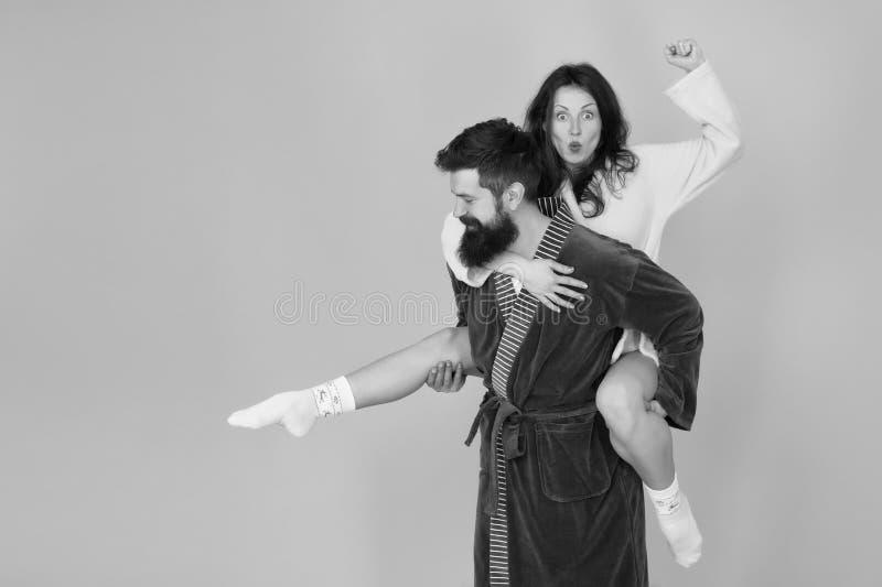 Knappe jonge mens die zijn rit van het meisjevervoer per kangoeroewagen geven Paar in badjassen die pret turkooise achtergrond he stock foto