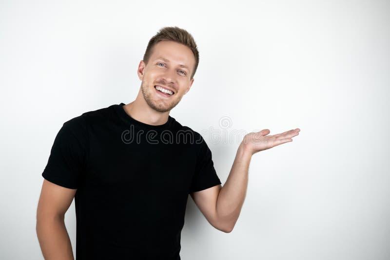Knappe jonge mens die zwarte t-shirt dragen die en exemplaarruimte glimlachen houden terwijl status geïsoleerd op witte achtergro royalty-vrije stock afbeelding