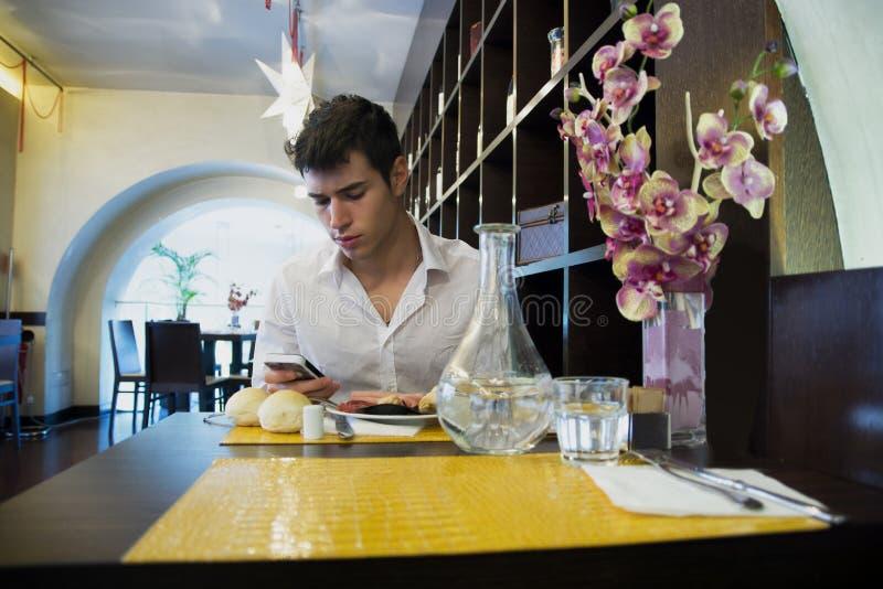 Knappe jonge mens in elegant restaurant die celtelefoon met behulp van royalty-vrije stock fotografie