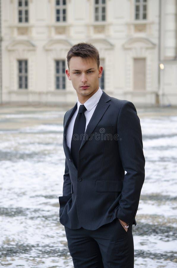 Knappe jonge mens en elegant paleis met sneeuw royalty-vrije stock foto's