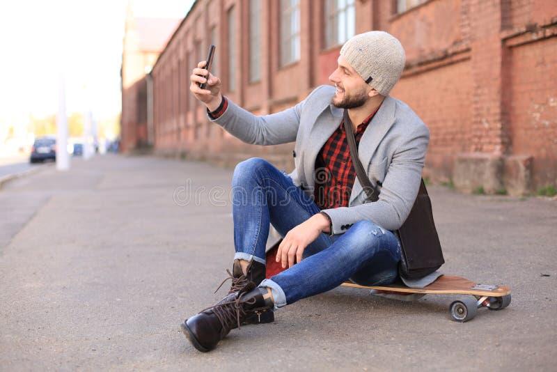 Knappe jonge mens in grijze laag en hoedenzitting op longboard en het nemen selfie op de straat in de stad royalty-vrije stock foto
