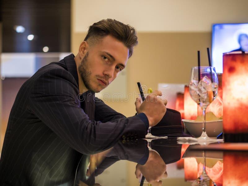 Knappe jonge mens het drinken cocktail bij barteller stock foto's