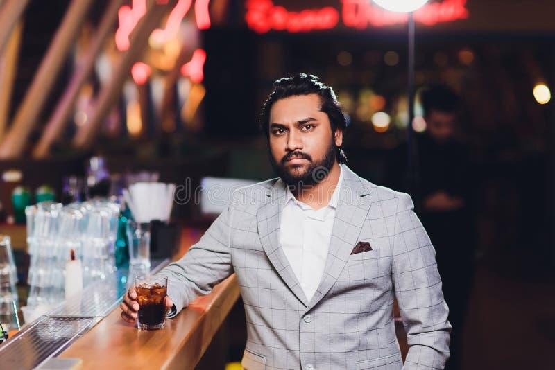 Knappe jonge mens het drinken cocktail bij barteller, die pak dragen stock foto's