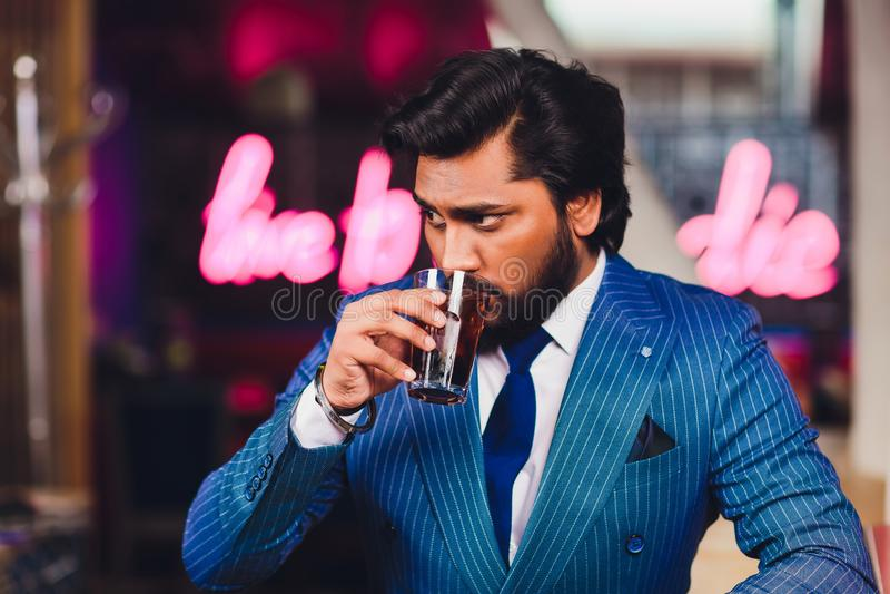 Knappe jonge mens het drinken cocktail bij barteller, die pak dragen royalty-vrije stock afbeeldingen