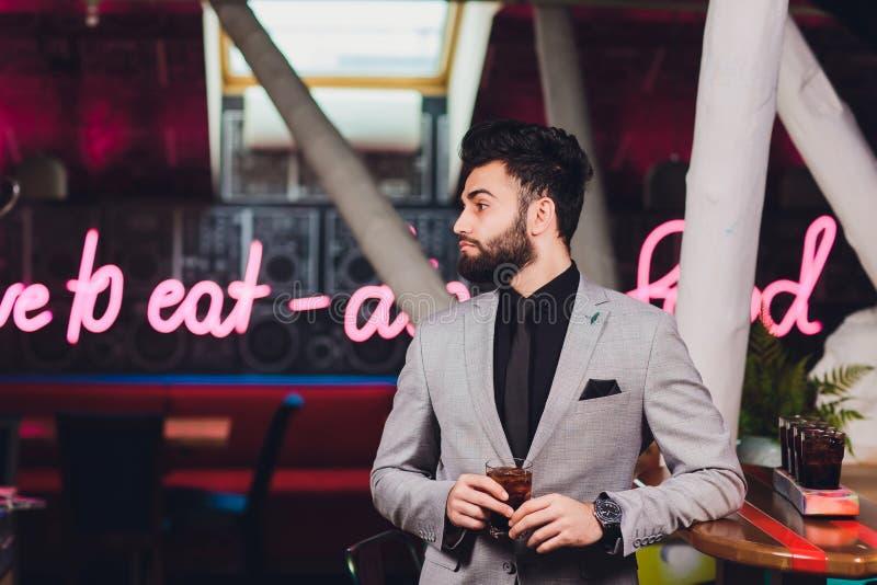Knappe jonge mens het drinken cocktail bij barteller, die pak dragen stock afbeeldingen