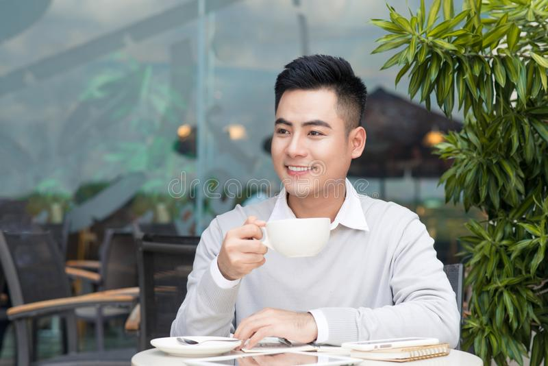 Knappe jonge mens het drinken koffie bij stad royalty-vrije stock afbeelding