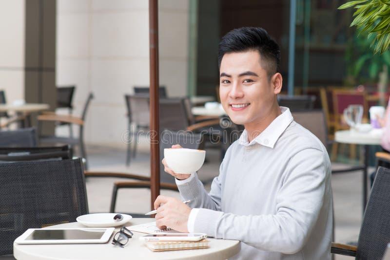 Knappe jonge mens het drinken koffie bij stad stock fotografie