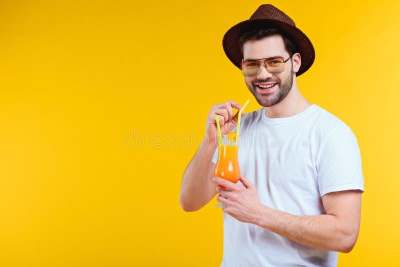 knappe jonge mens in hoed en zonnebril die de zomercocktail drinken en bij camera glimlachen royalty-vrije stock afbeelding