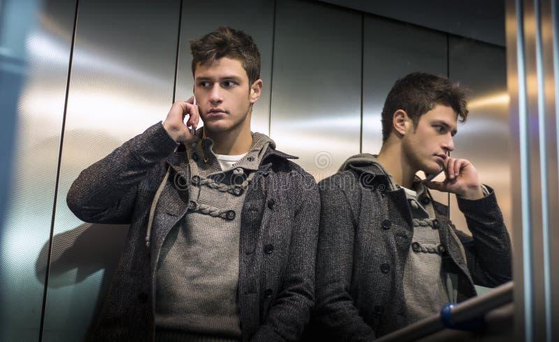 Knappe jonge mens in lift die (lift) celtelefoon met behulp van stock afbeeldingen