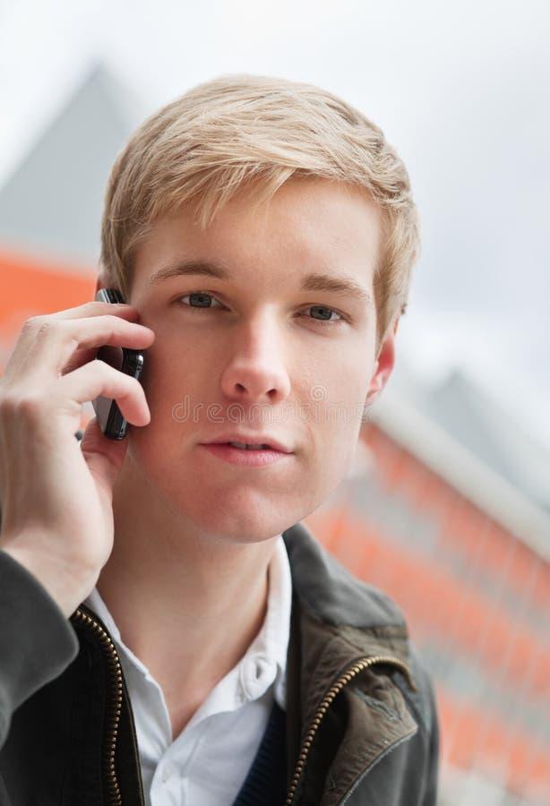 Knappe jonge mens met cellphone royalty-vrije stock afbeeldingen