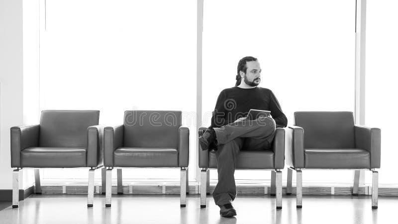 Knappe jonge mens met dreadlocks die zijn digitale tabletpc met behulp van bij een luchthavenzitkamer, moderne wachtkamer, met ba royalty-vrije stock fotografie