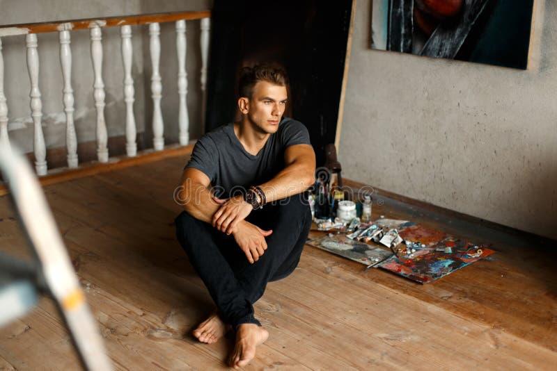 Knappe jonge mens met een grijze overhemdszitting in een kunststudio royalty-vrije stock afbeelding