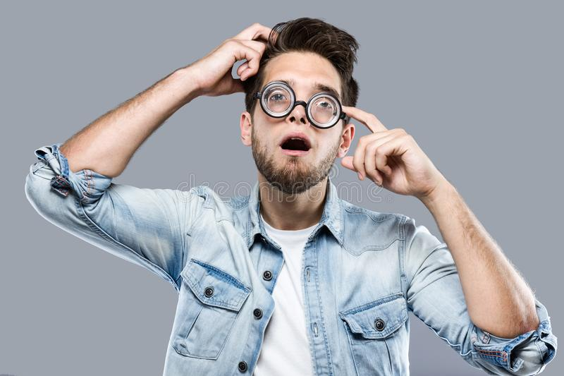 Knappe jonge mens met grappige glazen die en grappig gezicht over grijze achtergrond maken gekscheren stock fotografie