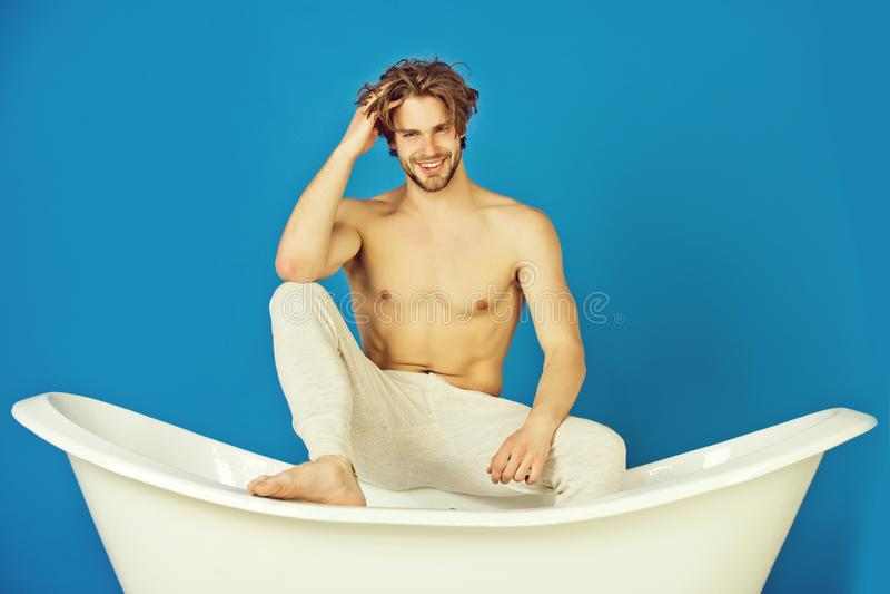 Knappe jonge mens met spierlichaamszitting in witte badkuip stock foto