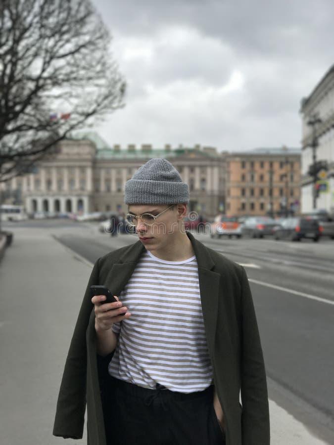 Knappe jonge mens met telefoon in St. Petersburg bij de St Isaac Kathedraal stock afbeelding