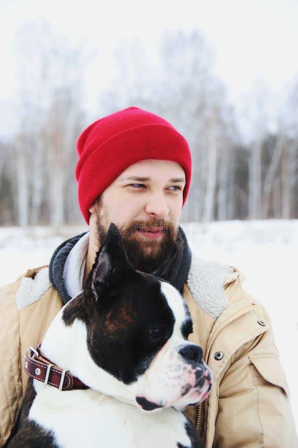 Knappe jonge mens met zijn bokserhond in openlucht stock fotografie