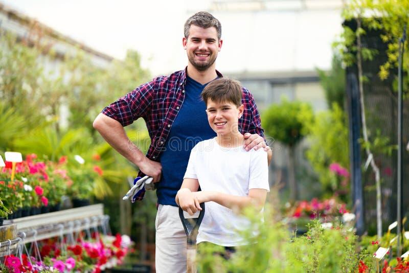 Knappe jonge mens met zijn zoon die camera in de serre bekijken stock foto
