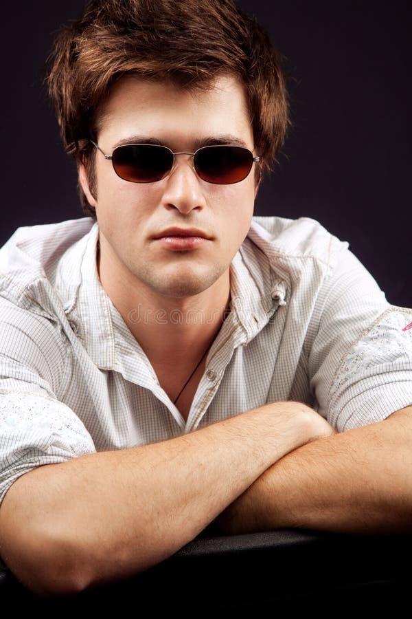 Knappe jonge mens met zonnebril stock afbeeldingen