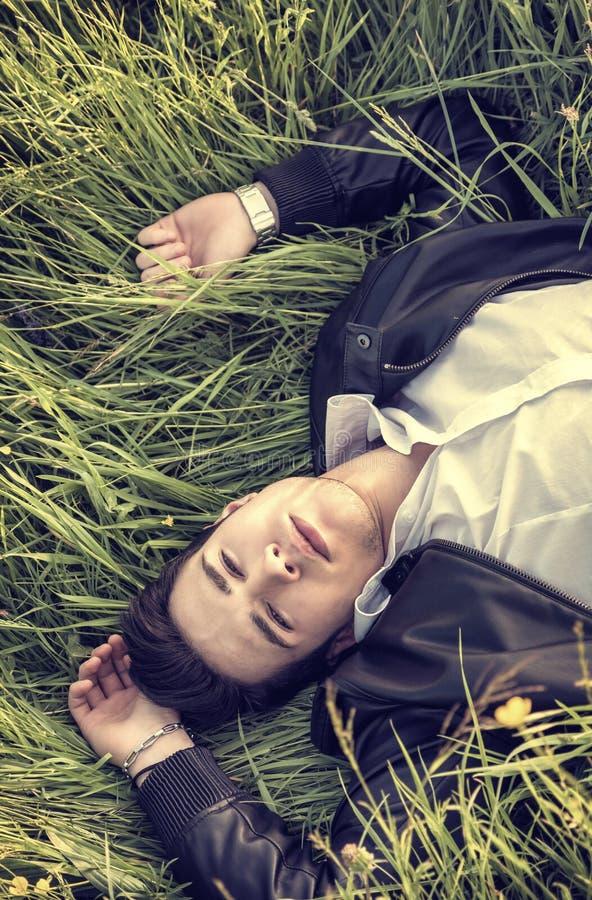 Knappe, jonge mens ontspannen die op gras liggen stock afbeelding