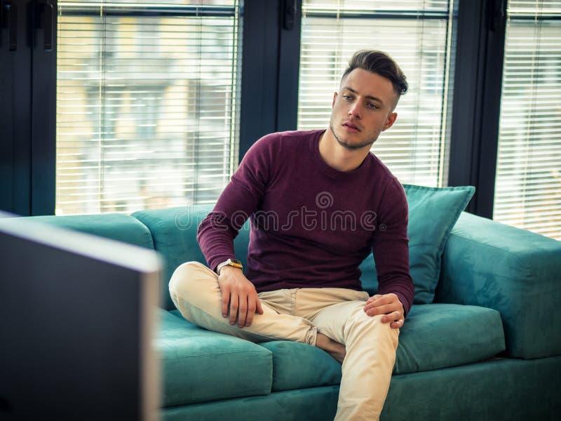 Knappe jonge mens op counch, die TV-afstandsbediening met behulp van stock foto's
