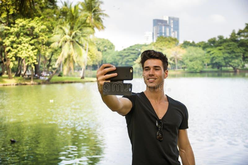 Knappe jonge mens in openlucht in stadspark royalty-vrije stock afbeelding