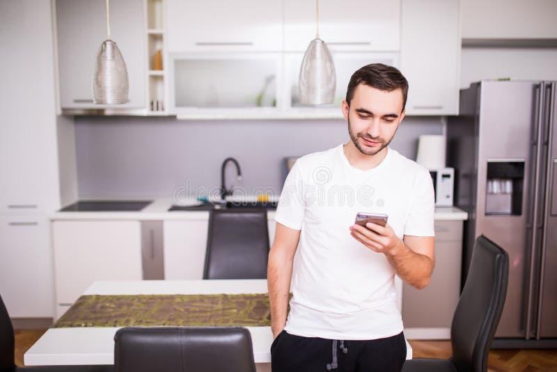 Knappe jonge mens in plaidoverhemd die en smartphone op de keuken bevinden zich gebruiken royalty-vrije stock afbeelding
