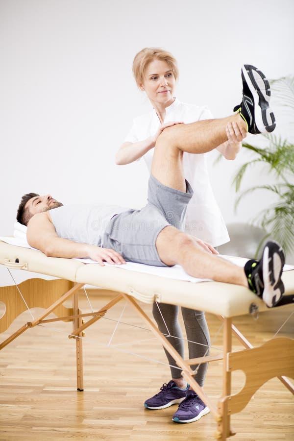 Knappe jonge mens tijdens fysiotherapiezitting met professionele arts royalty-vrije stock afbeelding