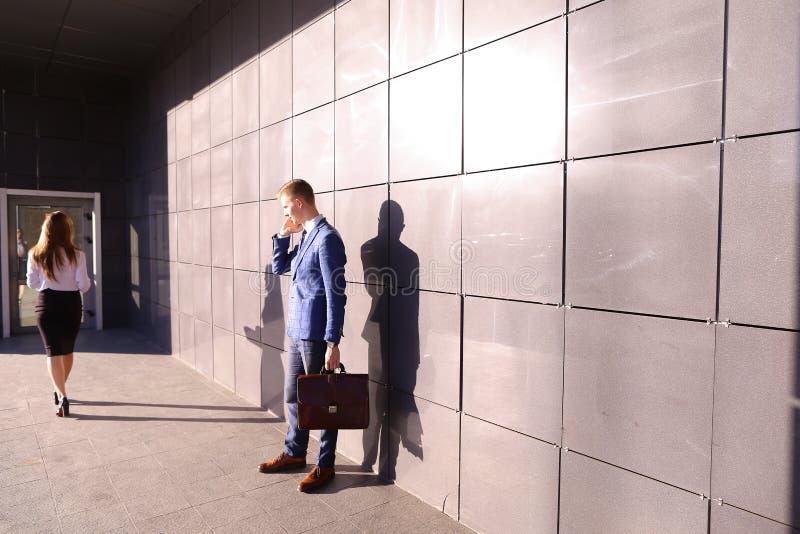Knappe jonge mens, zakenman die op telefoonpassen door beaut spreken royalty-vrije stock afbeelding