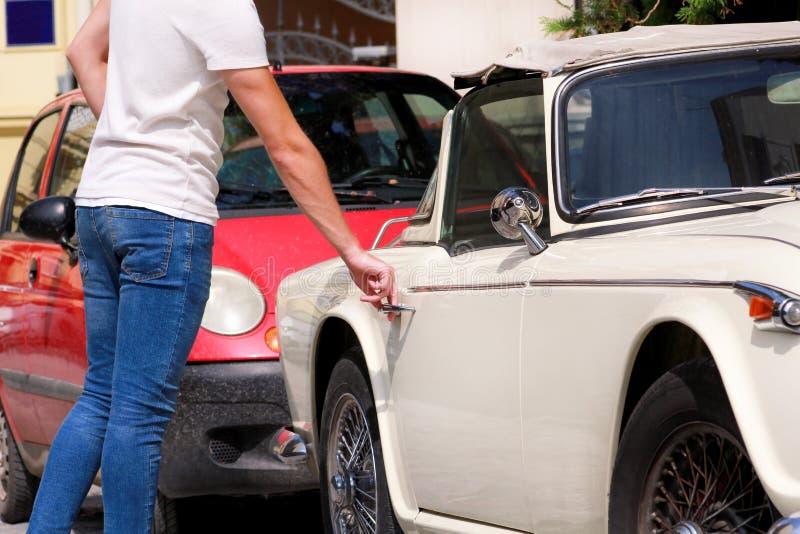 Knappe jonge mens in zonnebril die zich in stedelijke stadsstraat bevinden naast een oude retro auto Een kerel die en oude tijdop stock foto