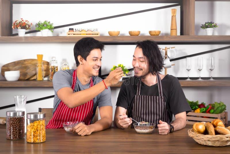 Knappe jonge mensen die ontbijt hebben samen, ??n mens het voeden graangewas aan andere in moderne eetkamerflat op weekend stock foto