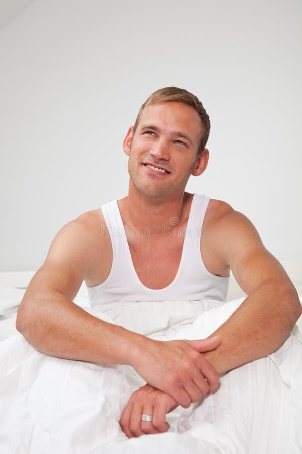 Knappe jonge mensenzitting die in bed denken stock afbeelding