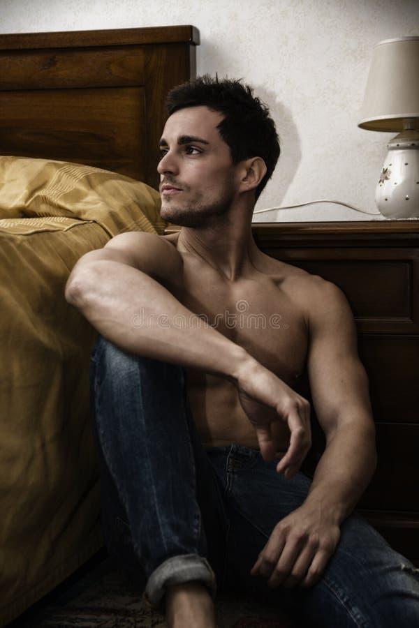 Knappe jonge mensenzitting door zijn bed royalty-vrije stock foto