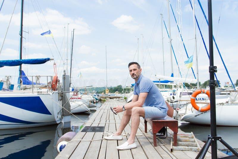 Knappe jonge mensenzitting op bank in dok van de baai tussen boten mens die op pijler weg kijken royalty-vrije stock afbeelding