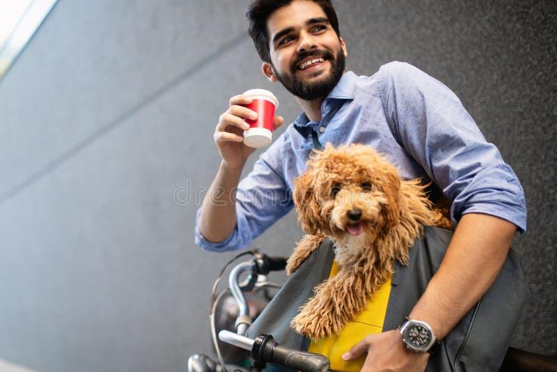 Knappe jonge mensenzitting op fiets en holdingskoffiekop op straat stock fotografie