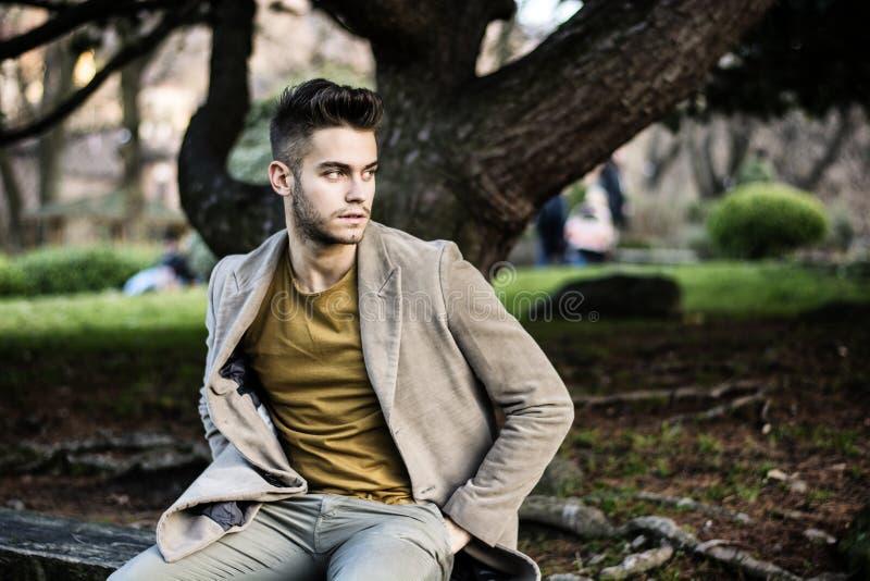 Knappe jonge mensenzitting in stadspark royalty-vrije stock foto