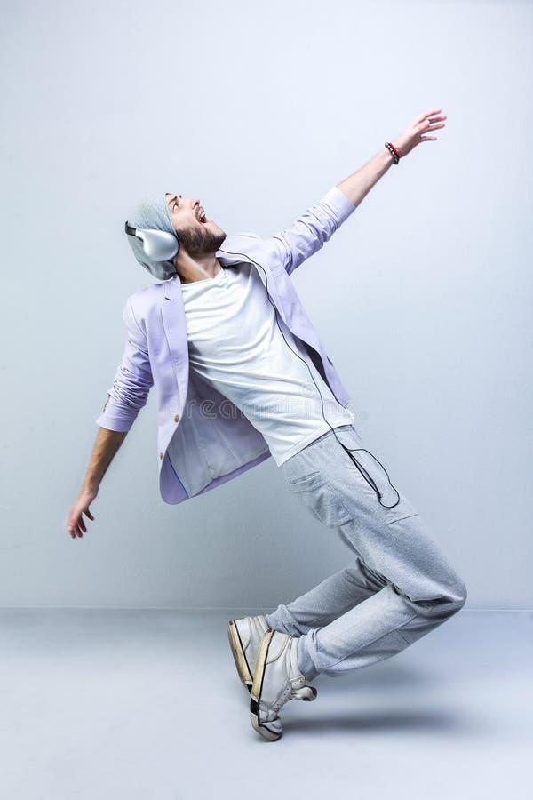 Knappe jonge modieuze mens in hoofdtelefoons het dansen stock afbeeldingen