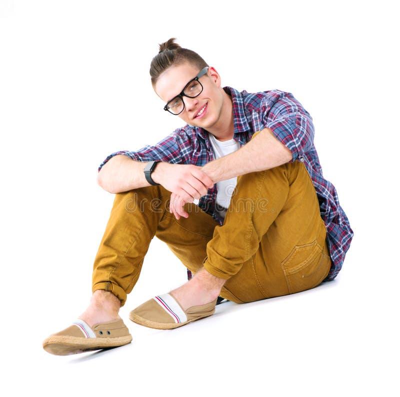 Knappe jonge modieuze mensenzitting op de vloer stock fotografie