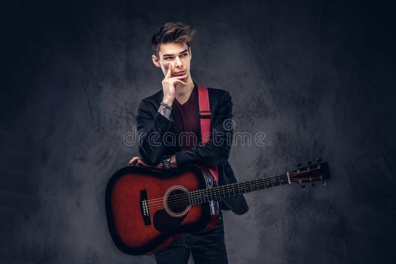 Knappe jonge nadenkende musicus met modieus haar in elegante kleren die met een gitaar in zijn handen stellen royalty-vrije stock afbeeldingen