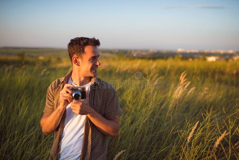 Knappe jonge reizigersmens met uitstekende camera, op een groene weideachtergrond Reisstemming fotografie royalty-vrije stock foto
