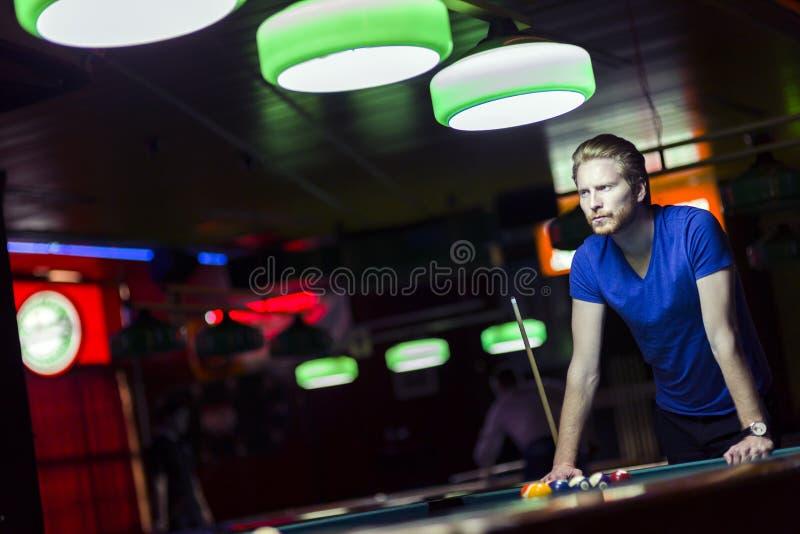 Knappe jonge snookerspeler die over de lijst buigen royalty-vrije stock foto