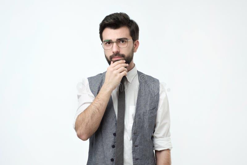 Knappe jonge Spaanse mens die peinzend terwijl status tegen witte achtergrond kijken royalty-vrije stock fotografie