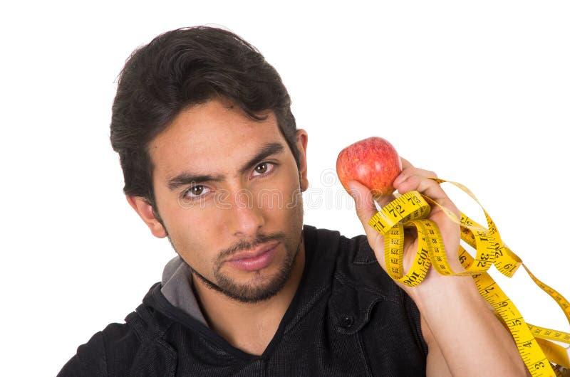 Knappe jonge sterke mens die rode appel houdt en stock fotografie