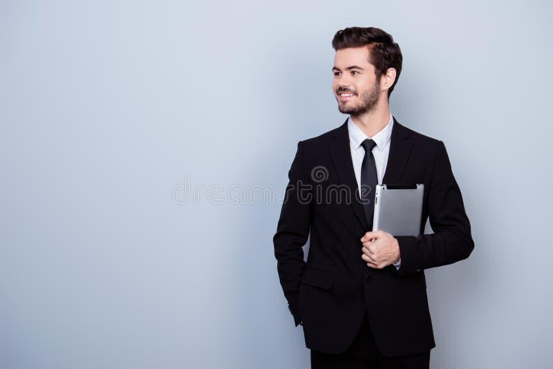 Knappe jonge succesvolle gelukkige zakenman in zwart kostuum holdin royalty-vrije stock afbeelding