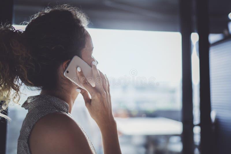Knappe jonge vrouw die met vrienden via moderne smartphone spreken terwijl het doorbrengen van haar tijd bij moderne stedelijke k royalty-vrije stock fotografie