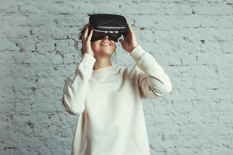 Knappe jonge vrouw die virtuele hoofdtelefoon dragen Het glimlachen hipster gebruikend VR-glazen Lege sweater Witte bakstenen muu royalty-vrije stock fotografie