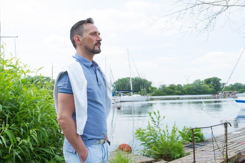Knappe jonge yachtman status op rivierpijler Mens die ver op zijn jacht onderzoeken Jonge zakenman met zijn jacht in jachthaven stock foto's