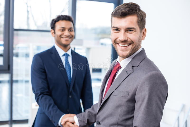Knappe jonge zakenlieden die handen schudden en bij camera glimlachen stock fotografie
